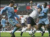 Spurs' Robbie Keane (centre) tussles with two Bolton players