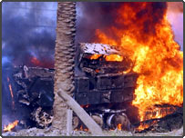 A US Army armoured vehicle burns on the airport highway in Baghdad, Iraq