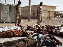 Iraqi officers stand by the dead bodies of Iraqi army recruits