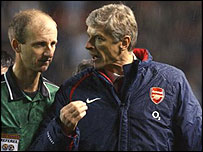 Arsene Wenger (right) berates referee Mike Riley after the game.