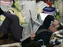 An elderly man lies on the floor and reads a newspaper at an evacuation centre in Nagaoka, northwest of Tokyo, 25/10/04