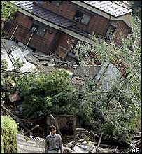 A villager walks past a damaged house sitting tilted on a slope in Nigorizawa village in Nagaoka city, northwest of Tokyo, Monday Oct 25, 2004