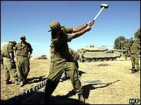 Israeli soldier fixes tank tracks on Gaza border