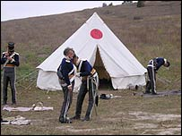 Men in uniforms prepare for the re-enactment