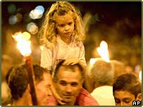 A girl on her father's shoulders as they participate in a pro-peace march towards the Knesset, Israel's parliament, to show support for the Israeli withdrawal from Gaza Strip