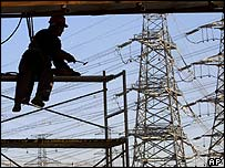 A worker repairs a bridge near power pylons in Beijing