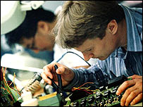 Male technicians working in microchip factory
