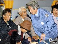 Japanese Prime Minister Junichiro Koizumi talks with people at a shelter in Nagaoka