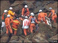Workers try to rescue a family of three from landslide (27/10/04)