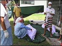 Men prepare to clean a corpse at the Thai military camp