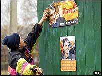 Un niño coloca el cartel del candidato de la oposición.