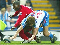Djibril Cisse and Jay McEveley tumble to the ground after the collision that broke the Frenchman's leg