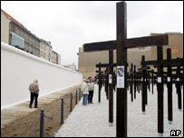 Wooden crosses stand next to a re-erected strip of the former Berlin Wall in Berlin