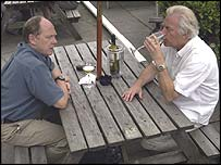 Two men enjoy wine in a pub garden