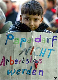 A young boy shows a poster reading