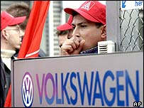 Volkswagen workers wearing IG Metall caps outside the factory gates