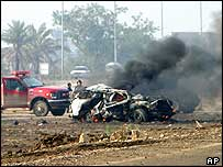 A vehicle burns along Baghdad's airport road after a suspected car bomb attack