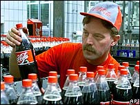 Worker inspects the labelling of bottles at the Coca-Cola factory in Halle, Eastern Germany