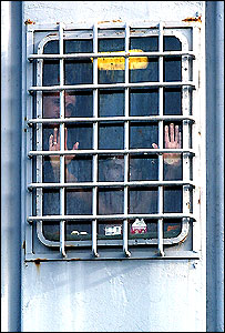 Inmates looking out of one of HMP Weare's windows