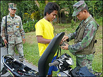 A Thai army soldier (R) checks on local youth along the highway leading to Sungei Golok, 03 November 2004, in southern Thailand