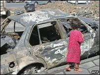 Una niña pasa junto a un coche destruido en Bagdad