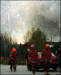 Fireworks light up the sky above firefighters