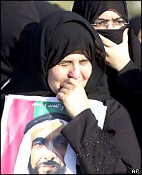 Women weep as they wait for the funeral cortege
