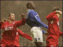 Former Liverpool striker Emile Heskey (centre) challenges for the ball in the air