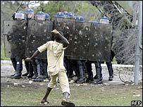 Manifestante tira piedras contra soldados franceses.