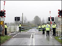 Police officers guard the scene of Saturday's crash