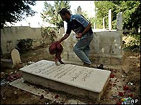 Man cleans gravestone of Yasser Arafat's sister