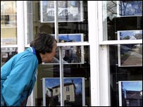 Woman looking into estate agent's window