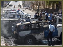 Iraqi policemen gather around smouldering police cars after a suicide attack