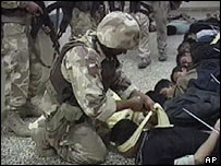 Image from TV of a US soldier blindfolding a man after troops entered Falluja hospital, in Iraq
