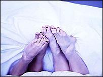 Painted toenails under a duvet
