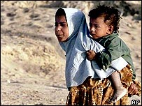 Afghan girl carrying boy on her back in Iranian refugee camp
