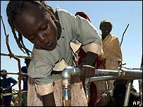 Displaced children fill containers with water in a camp in Darfur