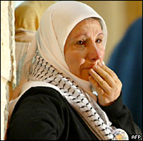 A Palestinian woman weeps as she hears news of Yasser Arafat's illness