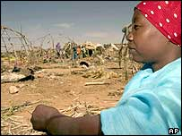 A refugee in Darfur looks at damaged homes at the El Geer camp near Nyala