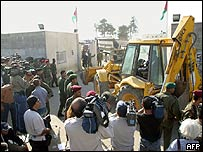 Journalists film bulldozers as they arrive at Yasser Arafat's Muqata compound in the West Bank