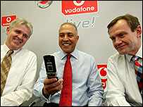 Vodafone boss Arun Sarin (c) and colleagues holding a 3G phone