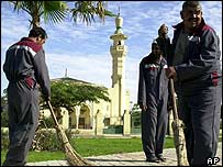 Workers clean street outside Cairo Airport's King Faisal bin Abdel Aziz Mosque