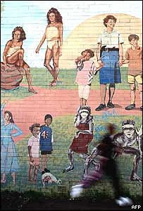 A jogger passes a mural featuring Aboriginal children by Australian artist Michael Byrt in the indigenous community of Redfern in Sydney, 15 October 2004