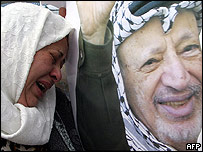 Woman crying in front of image of Yasser Arafat