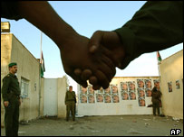 Holding hands in front of images of Yasser Arafat
