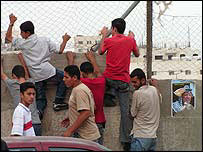 Palestinian boys climb up a fence to see Mr Arafat's grave, Ramallah