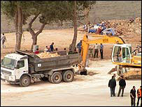 Vehicles clear earth as they dig Arafat's grave in the Muqata, Ramallah