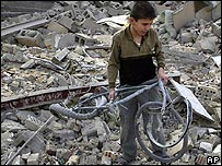 Iraqi boy with a damaged bicycle