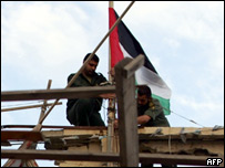 Palestinian security guard lowers the Palestinian flag to half-mast at Yasser Arafat's former headquarters in Gaza City
