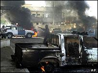 Vehicles burn near an Iraqi police station in Mosul, Iraq